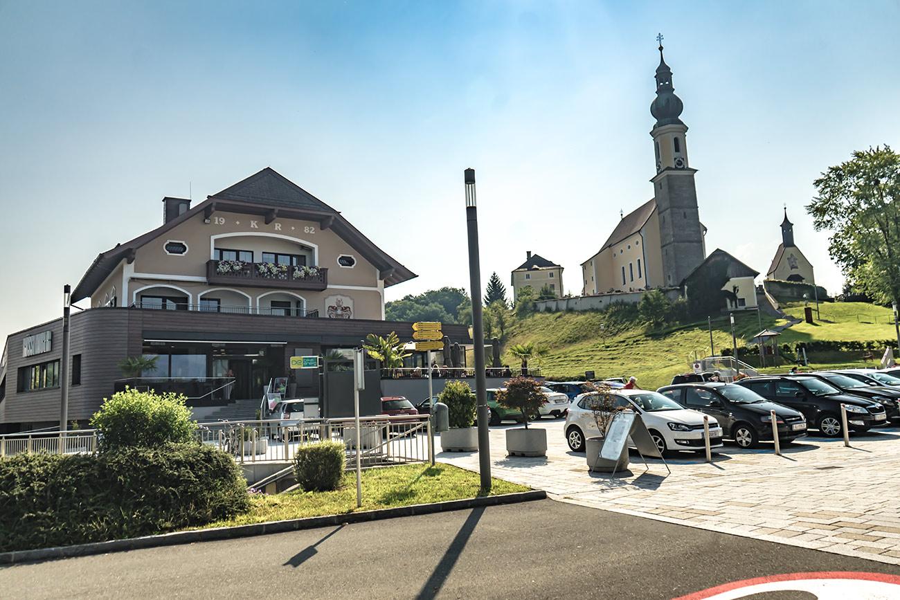 Dorfplatz mit Bäckerei Rösslhuber und Pfarrkirche Bergheim (c) STADTBEKANNT Zohmann